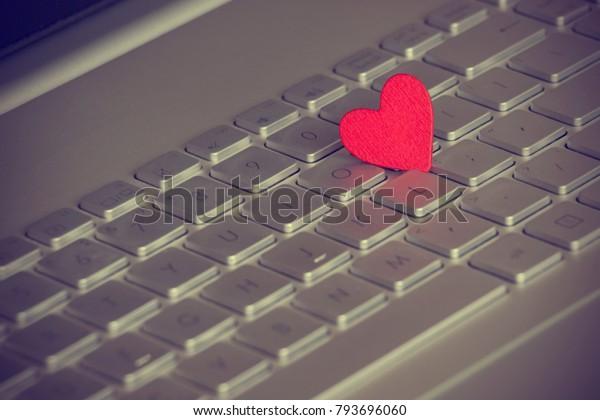 A red rural heart on a laptop keyboard. Vignette
