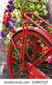 red rusty bicycle tire in front of blooming colorful bushes in Amsterdam, Holland