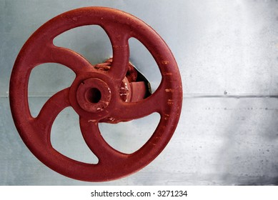 red rusty industrial faucet wheel on silver background