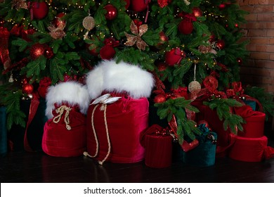 Red sack santa claus with gifts near Christmas tree. Beautiful decorated living room for Christmas. Xmas gifts in cozy living room. Light garlands on Christmas tree home. Bag santa with presents