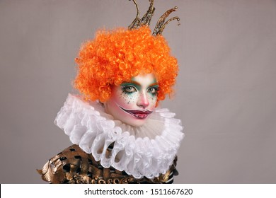 Red sad clown . Beautiful girl with bright clown makeup with red wig and painted smile. horizontal frame, gray background .