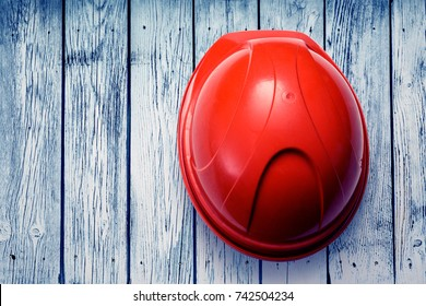 Red safety helmet from the top on wooden