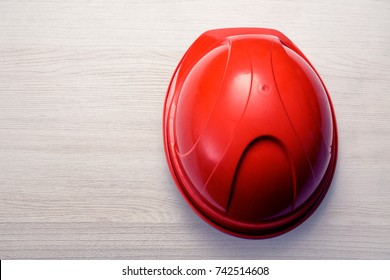 Red safety helmet from the top on wooden background