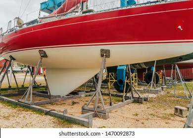 Red sailboat on the land, yacht in a dockyard for a repair, fixing a boat