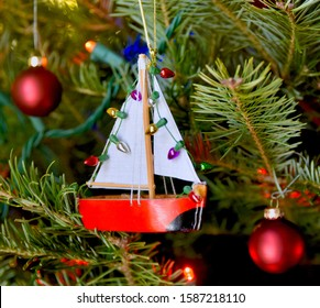 Red sailboat ornament hanging on a Christmas tree.  Closeup.