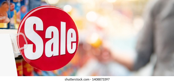 Red sale label on product shelf in supermarket with blurred male shopper choosing food package in the background. shopping lifestyle in grocery store concept