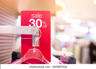Red sale sign 30% discount on clothing rack in modern shopping mall or department store with copy space. Retail shop promotional event, new product discount, or business marketing advertising concept