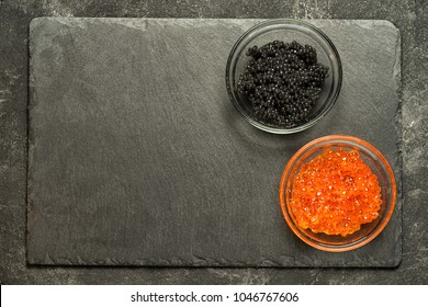 red salmon roe and black stugeon caviar on the black stone board on a black table, top view with copy space.