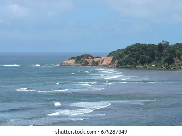 Red Sand Mountain of the Caribbean Island and Atlantic Ocean with waves