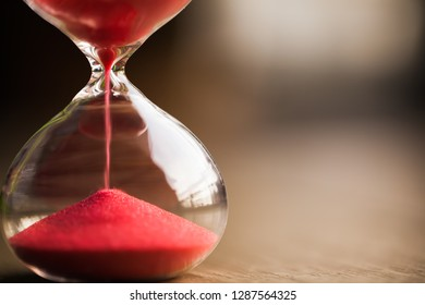 Red sand running through the bulbs of an hourglass measuring the passing time in a countdown to a deadline, on a dark wooden background with copy space.