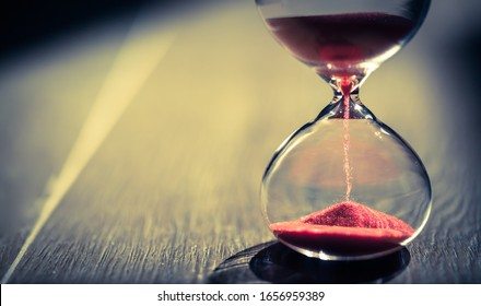 Red sand running through the bulbs of an hourglass measuring the passing time in a countdown to a deadline, on a wooden floor background with copy space. Under sunlight.