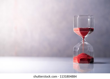 Red sand running through the shape of modern hourglass on white table.Time passing and running out of time. Urgency countdown timer for business deadline concept with copy space