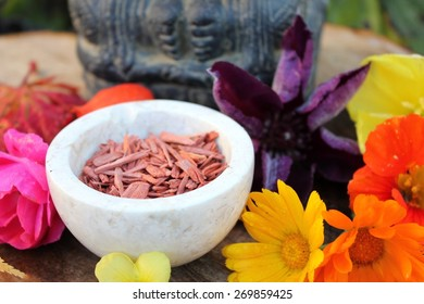 Red Sandalwood chips cut (santali rubri from Gabun) in a stone bowl ritual offering to the indian elephant god ganesha with different fall / autumn flowers and leaves (rose, calendula) in vivid colors
