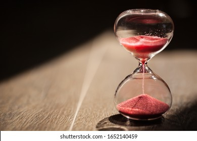 Red sandglass, hourglass or egg timer on wooden floor with shadow showing the last second or last minute or time out. With copy space.