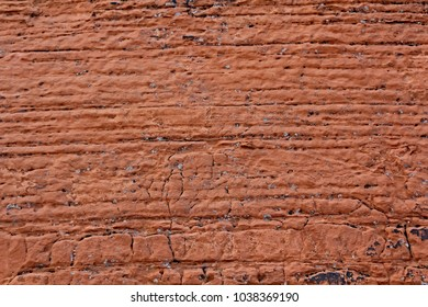 Red sandstone background, weathered horizontal lines, pitted and cracked natural.