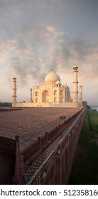 Red sandstone base of the rear of Taj Mahal rises out of the bank of the Jamuna river at sunrise in Agra, India. Fiery red sky copy space