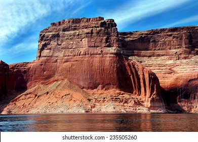 Red sandstone cliff reaches for blue sky along the shores of Lake Powell in Arizona.