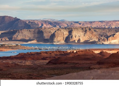 Red sandstone leads into the busy Wehweap Marina on Lake Powell then to pale sandstone cliffs lit by morning sunshine and darker and larger mountains in the distance.