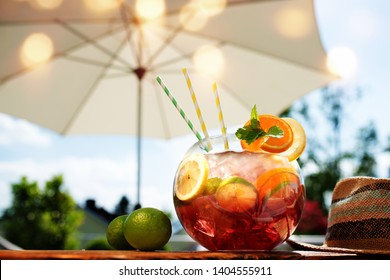 Red sangria cocktail on a summer terrace with a parasol