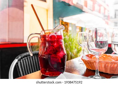 Red sangria glass jar made of red wine and fruits near empty glass on restaurant terrace table on sunny day on background of colorful historical buildings