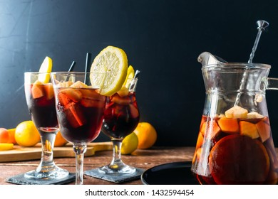 Red Sangria in wine glasses with a sangria pitcher, garnished with drinking straw and lemon slices, on a wooden table and dark background. Copy space