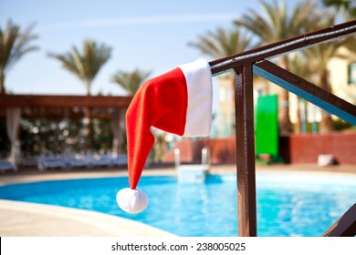 Red Santa Claus hat hanging on a wooden railing next to the pool a summer day