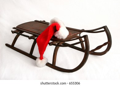 Red Santa Claus hat lying on antique wooden sled