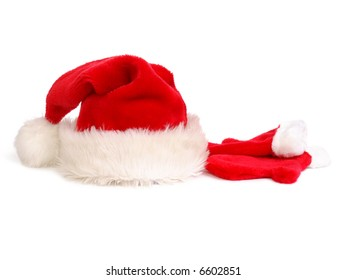 Red santa claus hat and pair of gloves over white background