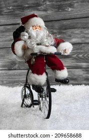 Red Santa Claus making christmas shopping with his bike. Funny idea  for xmas decoration.