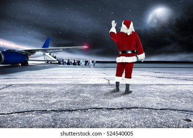 Red santa claus on airport and big plane with few people