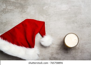 Red santa hat and a glass of beer on a concrete table