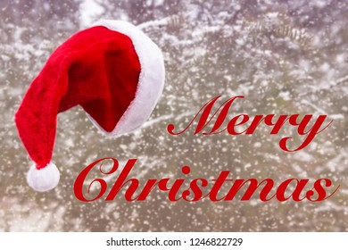 red santa hat hanging from a tree in the snow and the words Merry Christmas