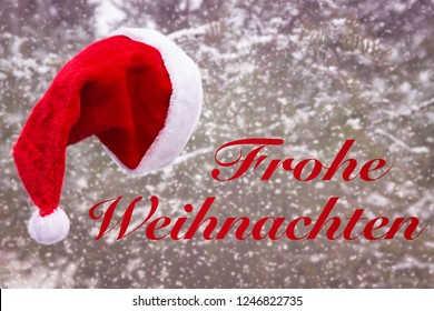 red santa hat hanging from a tree in the snow and the german words for Merry Christmas