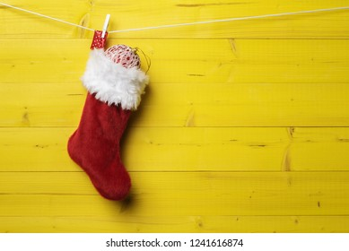 Red Santa stocking with Christmas ball over yellow wooden background. Xmas and New Year concept.