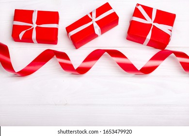 Red satin ribbon and box isolated on white background. The concept of the holidays