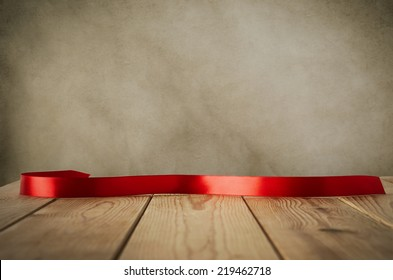 A red satin ribbon, curved and facing front to provide copy space for message, placed on a wood plank table against parchment background.  Vintage style.