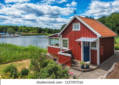 Red scandinavian wooden house on the lake with beautiful blue sky.