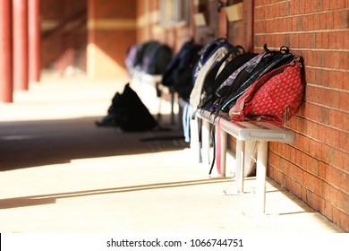 Red school bag in focus on a bench seat in a school yard. image of a number of  backpacks or duffle bags lined up outside a classroom at a high school or middle school. no students, long shadows.