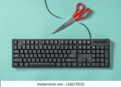 Red scissors and a black keyboard with a cut wire. Idea and concept for the topic of censorship or freedom of the press.
