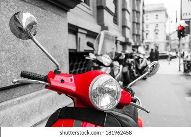 red scooter in the city of Milan with black and white surrounding