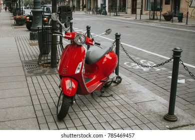 Red scooter parked on the pavement. Europe street photo background.