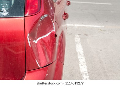 Red scratched car with damaged paint in crash accident or parking lot and dented damage of metal body from collision