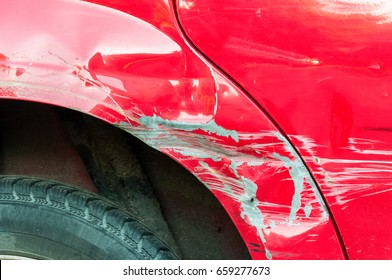 Red scratched car with damaged paint in crash accident or parking lot.