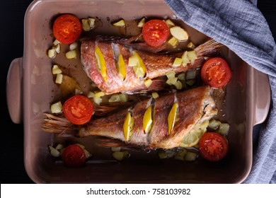 Red sea perch or red grouper with tomatoes and lemon baked and cooked on dark. Top view