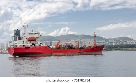 A red sea ship in the sea, against a background of white high-rise buildings.