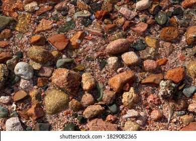 Red Sea Wave on Wet Red Sand and Stones. Natural Texture Background Terracotta Granite Pebbles, Schist and Sands