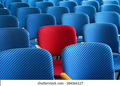 Red seat as an eyecatcher in the middle of rows of empty blue seats, conceptual image