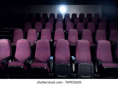 red seats in empty dark movie theater with back light