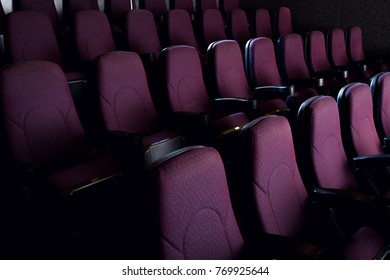 red seats in empty dark movie theater