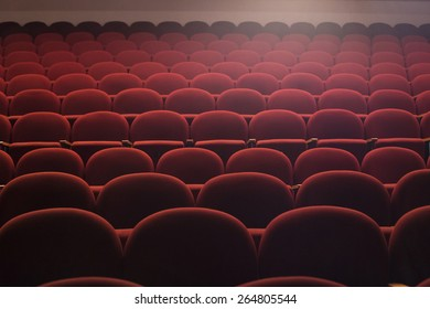 Red seats in theater hall with lens flare, wide shot